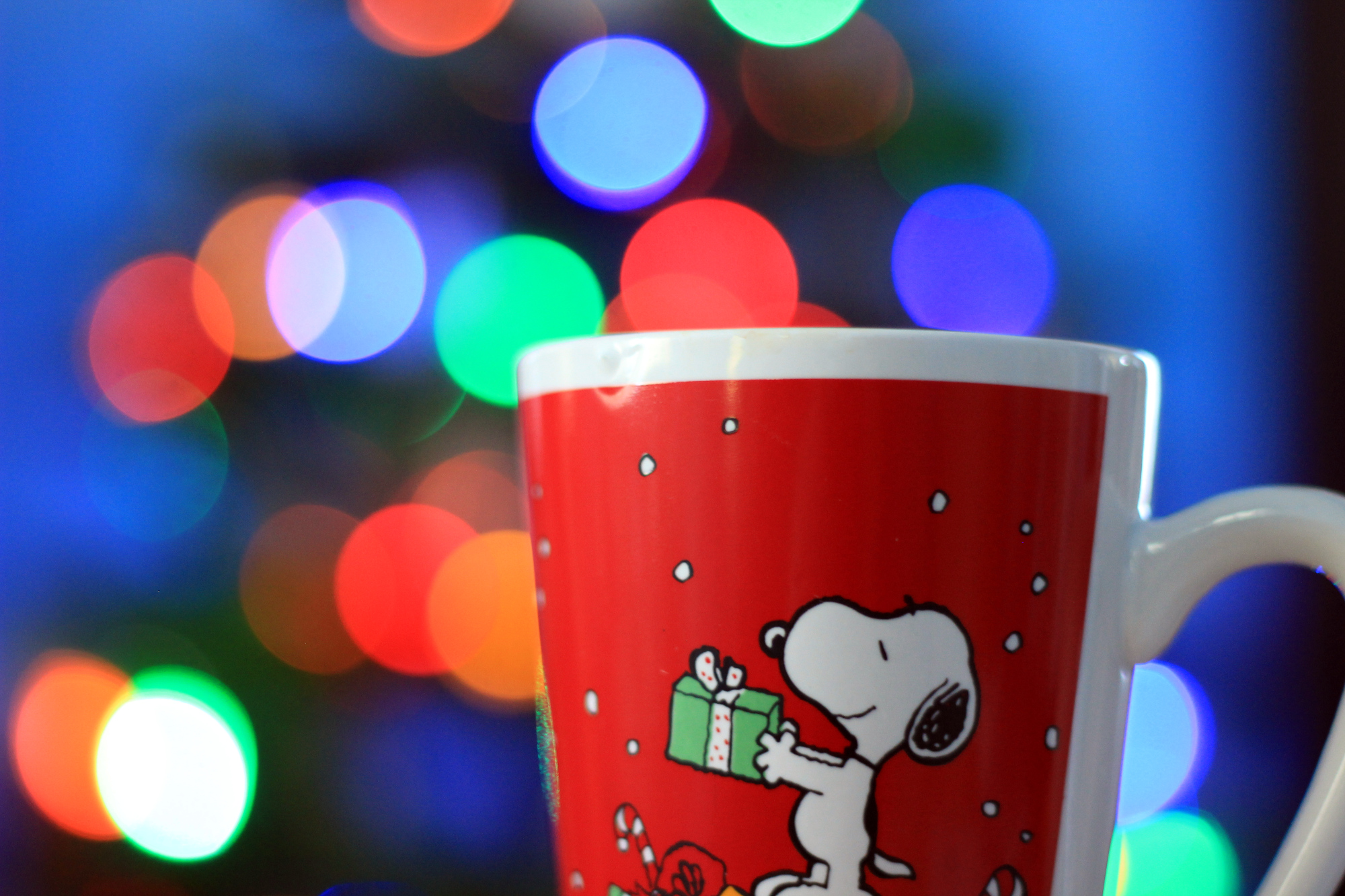 Snoopy coffee mug with the lit tree in the background