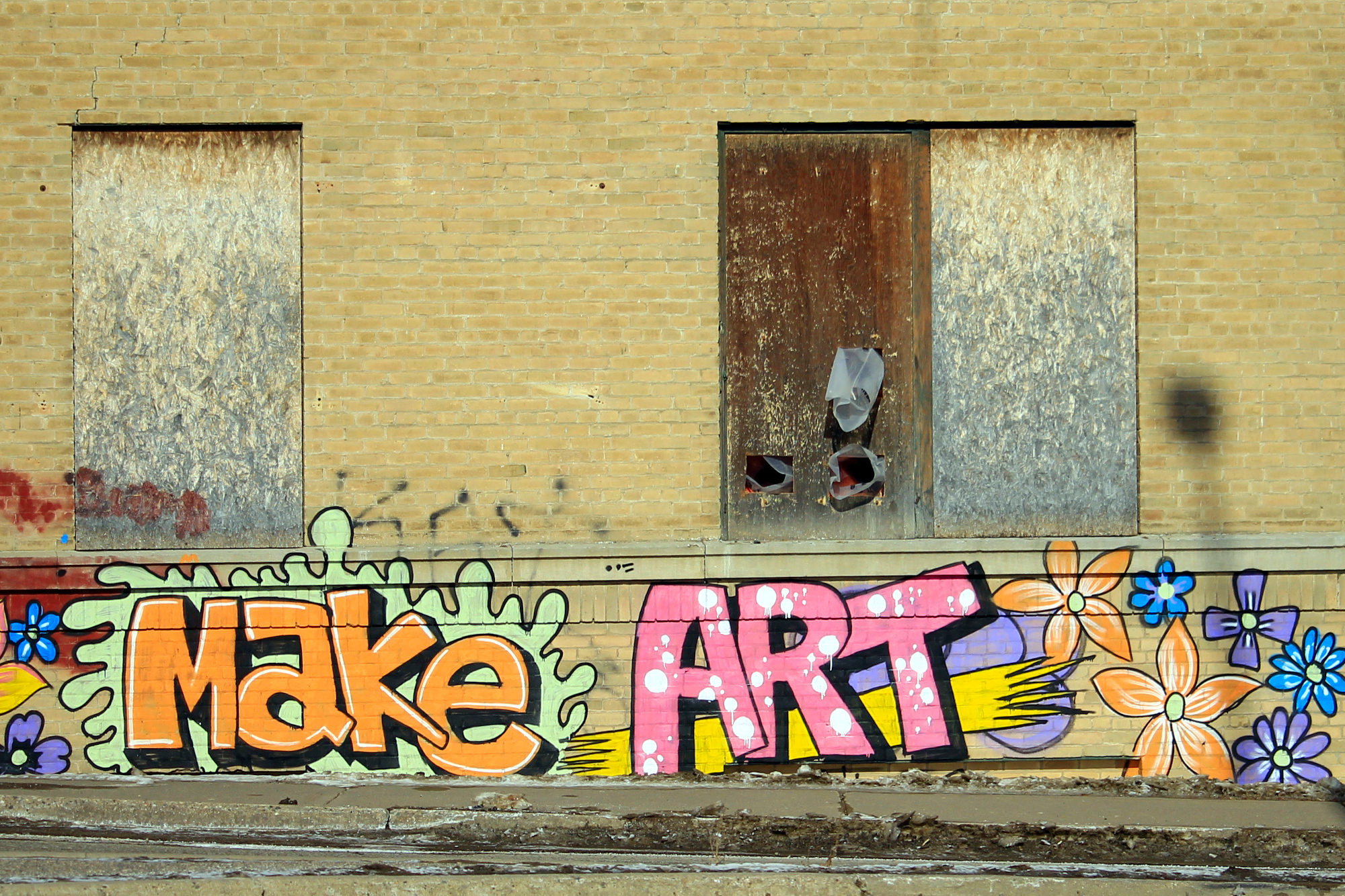 MAKE ART spray-painted on a building