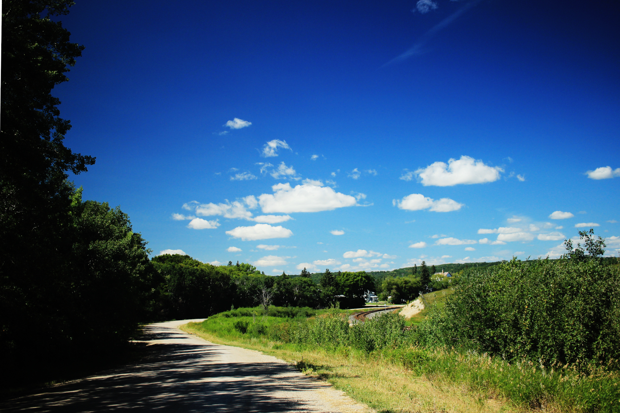 Blue sky with a few clouds above the road and the railroad